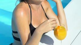 Señora alegre sonriente en gafas de sol elegantes y cóctel de consumición del bikini en piscina almacen de metraje de vídeo