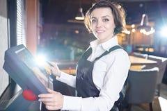 Señora alegre usando el terminal de la posición en restaurante imagen de archivo