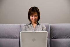 Señora asiática en traje del asunto, usando un ordenador Fotos de archivo