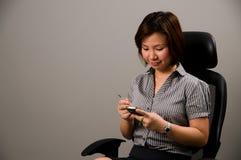 Señora asiática en traje del asunto, usando un PDA Imágenes de archivo libres de regalías