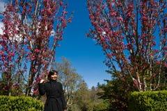 Señora asiática en un jardín de flores rosado Imágenes de archivo libres de regalías