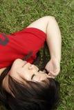 Señora asiática que duerme en hierba Foto de archivo