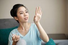 Señora asiática que mira clavos pintados imagen de archivo libre de regalías