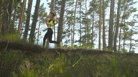 Señora atlética hermosa en el uniforme que corre alrededor en el bosque metrajes