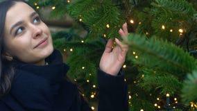 Señora atractiva alegre que mira las decoraciones de la Navidad, para días de fiesta que esperan metrajes