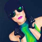Señora atractiva brillante en fondo negro en las gafas de sol de moda a Fotos de archivo