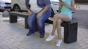 Señora atractiva con el smartphone que da vuelta lejos al individuo gordo, sentándose en banco, contraste metrajes