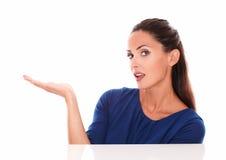 Señora atractiva en camisa azul con la palma para arriba Foto de archivo