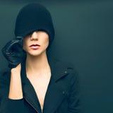 Señora atractiva en fondo negro en guantes y autu de moda del sombrero Fotos de archivo