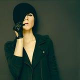 Señora atractiva en fondo negro en guantes y autu de moda del sombrero Fotografía de archivo