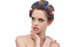 Señora atractiva en los rodillos del pelo que presentan y que miran lejos Imagen de archivo libre de regalías