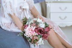 Señora atractiva hermosa en traje y ramo blancos elegantes Imagen de archivo
