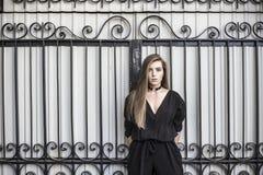 Señora atractiva atractiva hermosa joven que se coloca cerca del negro para Fotos de archivo libres de regalías