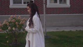 Señora atractiva hermosa joven que va abajo de la calle con un smartphone en sus manos almacen de metraje de vídeo