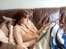Señora atractiva madura que pone en el sofá que lee un libro para relajarse foto de archivo