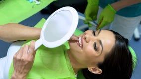 Señora atractiva que mira el resultado de la colocación del sellante, odontología cosmética foto de archivo libre de regalías