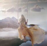 Señora atractiva que se sienta en el oscilación sobre el lago tranquilo Imagenes de archivo