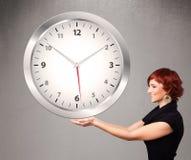 Señora atractiva que sostiene un reloj enorme Imagenes de archivo