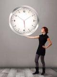 Señora atractiva que sostiene un reloj enorme Imagen de archivo