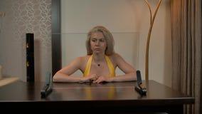 Señora atractiva atractiva que trabaja con la exhibición transparente metrajes