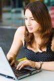 Señora bastante caucásica de los jóvenes que usa la computadora portátil al aire libre Fotos de archivo