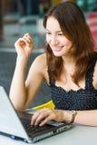Señora bastante caucásica de los jóvenes que usa la computadora portátil al aire libre Foto de archivo libre de regalías