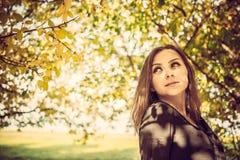 Señora bastante elegante de los jóvenes que presenta cerca de árbol del colourfull en el otoño fotografía de archivo