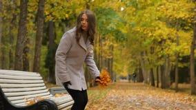 Señora bastante joven que espera alguien que vaga en el parque en otoño El sentarse en el banco y el esperar ha terminado almacen de video