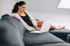 Señora bastante joven que se sienta en Internet que practica surf del sofá Foto de archivo libre de regalías