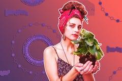 Señora bonita agradable atractiva que sostiene una planta fotografía de archivo