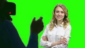 Señora bonita del negocio que presenta para la cámara en la pantalla verde almacen de video