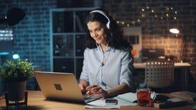 Señora bonita en auriculares que escucha la música en la oficina oscura que trabaja con el ordenador portátil metrajes