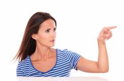 Señora bonita en camiseta azul que señala a su izquierda Imagen de archivo libre de regalías