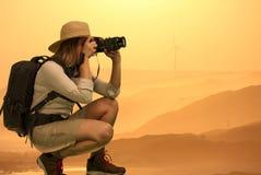 Señora bonita en Safari Dress que toma las fotografías en la puesta del sol Fotos de archivo