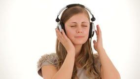 Señora bonita joven In Earphones Listening a la música metrajes