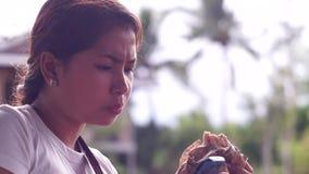 Señora bonita joven que come la hamburguesa almacen de metraje de vídeo