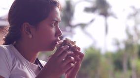 Señora bonita joven que come la hamburguesa almacen de video
