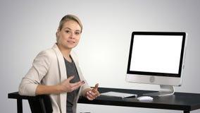 Señora bonita joven que habla con la cámara y que muestra algo en la pantalla del ordenador en fondo de la pendiente imagen de archivo