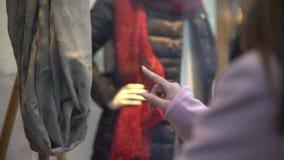Señora bonita joven que mira la ropa en la ventana de la tienda, soñando para comprar, ningún dinero almacen de metraje de vídeo