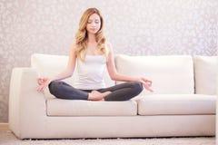 Señora bonita que hace yoga en el sofá imagen de archivo