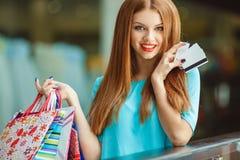 Señora bonita que muestra la tarjeta de crédito en la alameda Fotos de archivo libres de regalías
