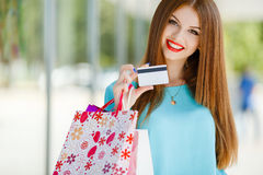 Señora bonita que muestra la tarjeta de crédito en la alameda Imagen de archivo