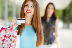 Señora bonita que muestra la tarjeta de crédito en la alameda Imágenes de archivo libres de regalías
