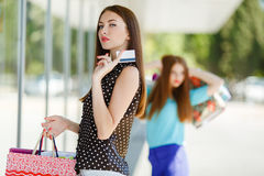 Señora bonita que muestra la tarjeta de crédito en la alameda Imagenes de archivo