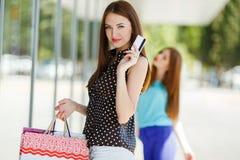Señora bonita que muestra la tarjeta de crédito en la alameda Fotografía de archivo