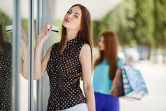 Señora bonita que muestra la tarjeta de crédito en la alameda Fotografía de archivo libre de regalías