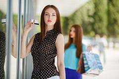 Señora bonita que muestra la tarjeta de crédito en la alameda Imagen de archivo libre de regalías