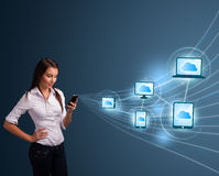 Señora bonita que pulsa en smartphone con la computación de la nube Foto de archivo