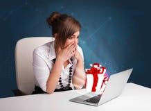 Señora bonita que se sienta en el escritorio y que pulsa en la computadora portátil con actual BO Imagenes de archivo