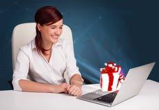Señora bonita que se sienta en el escritorio y que pulsa en la computadora portátil con actual BO Foto de archivo libre de regalías
